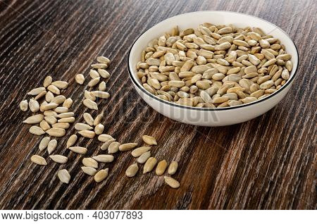 Peeled Sunflower Seeds In White Bowl, Scattered Seeds On Dark Wooden Table