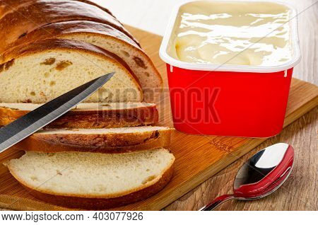 Slices Of Bread With Raisin, Kitchen Knife, Red Plastic Box With Creamy Cheese On Bamboo Cutting Boa