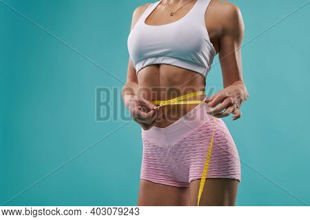 Closeup Of Body And Flat Belly Of A Beautiful Fit Woman Measuring Her Wait Using Measure Tape. Isola