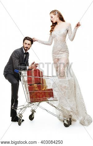 Gorgeous couple of young people in luxury evening dresses posing with a supermarket trolley full of gifts. Full length portrait on a white background. Wedding, holidays. Shopping concept.