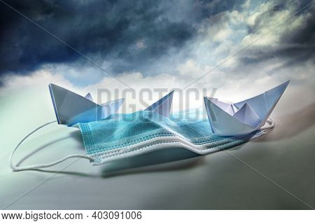 Three Paper Boats Struggle Against Sinking On A Surgical Face Mask Under A Stormy Sky, Metaphor For