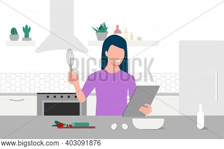 A Young Woman Looks On Tablet And Cooking By Online Video Tutorial In Her Kitchen. Online Culinary S