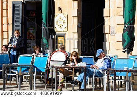 Mosta, Malta - April 2, 2017 - Tourists Relaxing At A Pavement Cafe In The Town Centre, Mosta, Malta