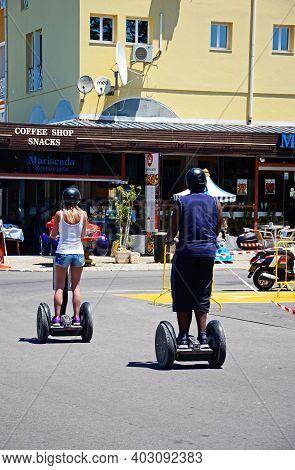 Vilamoura, Portugal - June 6, 2017 - Young Couple Riding On Segways, Vilamoura, Algarve, Portugal, E