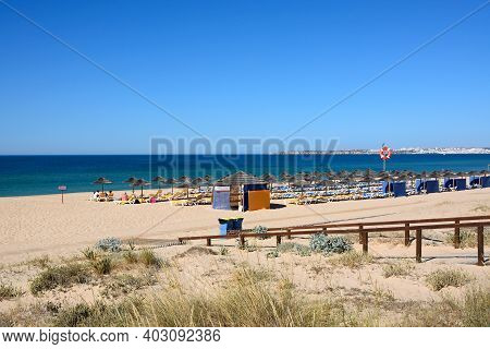 Alvor, Portugal - June 7, 2017 - Tourists Relaxing On The Sandy Beach With Views Towards The Atlanti