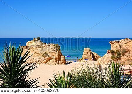 Portimao, Portugal - June 7, 2017 - Tourists Relaxing On The Beach With Views Across The Ocean And Y