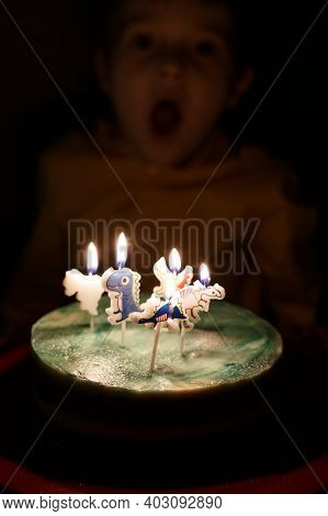 Adorable Five Year Old Kid Celebrating His Birthday And Blowing Candles On Homemade Baked Cake, Indo