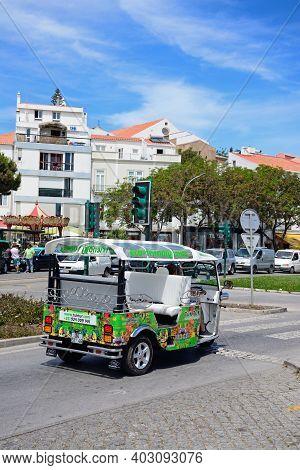Lagos, Portugal - June 9, 2017 - Eco-friendly Tuk Tuk Waiting At Traffic Lights Along The Avenida Do