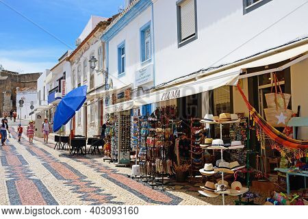 Lagos, Portugal - June 9, 2017 - Shops And Pavement Cafes Along The R 25 De Abril Shopping Street In