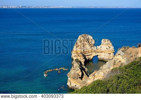 Lagos, Portugal - June 10, 2017 - View Of Rocks In The Sea With Tourists In Canoes And Views Towards