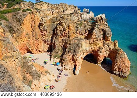 Portimao, Portugal - June 10, 2017 - Elevated View Of The Cliffs With Tourists Relaxing On A Seclude