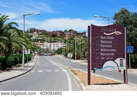 Silves, Portugal - June 10, 2017 - Approach Road To The Town With A Welcome Sign In The Foreground A