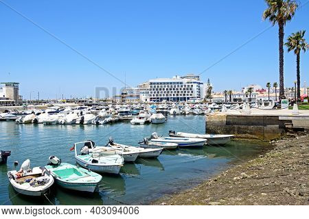 Faro, Portugal - June 12, 2017 - Small Motor Boats Moored In The Marina With A Waterfront Hotel To T