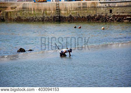 Tavira, Portugal - June 12, 2017 - Fisherman Wading Along The River Gilao, Tavira, Algarve, Portugal