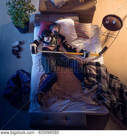 Sweet Dreams. Top View Of Young Professional Hockey Player Sleeping At His Bedroom In Sportwear With
