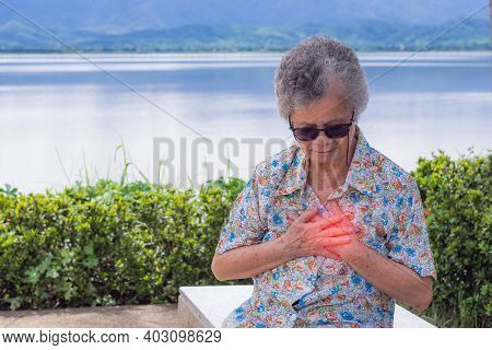 An Elderly Woman Clutching Her Chest In Pain At The First Signs Of Angina Or Myocardial Infarction O