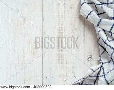 View From Above On White Wooden Table With Linen Kitchen Towel Or Textile Napkin. Blue Tablecloth On