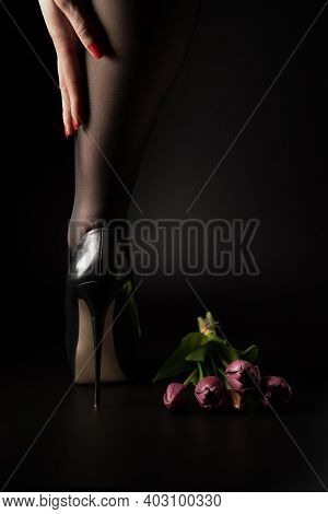 One Leg Of A Woman In Black Tights And High Heels And A Bouquet Of Flowers On A Black Background.