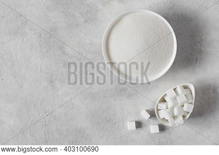 White Sugar Crystals And Cubes Of Refined Sugar In A Bowl Top View On Grey Concrete Table.