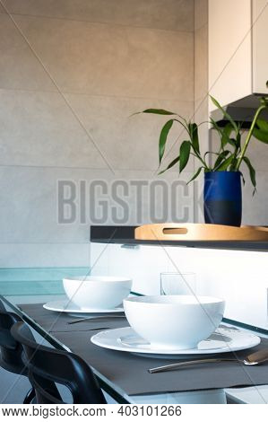 Table Settled For Two In A Modern Kitchen With White Dishes And Glasses. Blue Vase With A Plant On A