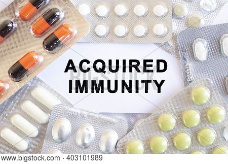 Text Acquired Immunity On A White Background. There Are Different Medicines Around. Medical Concept.