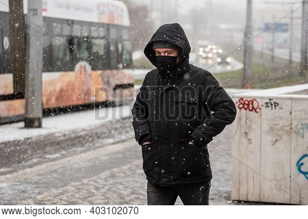 Prague, Czech Republic. 01-12-2021. Man Walking To Catch The Tramway On A Snowing Day With Mask Duri