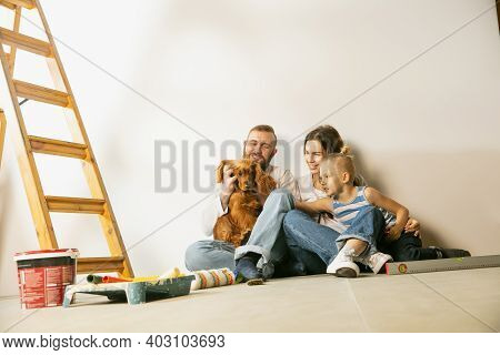 Young Couple, Family Doing Apartment Repair Together Themselves. Mother, Father And Son Doing Home M