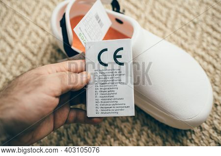Paris, France - Dec 13, 2020: Pov Male Hand Holding Paper Advertising Tag Of Crocs At Work Comfortab