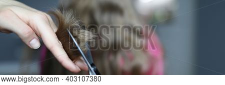 Close-up Of Mother Holding Metal Scissors And Cutting Strand Of Luxury Childs Hair. Home Hairdresser