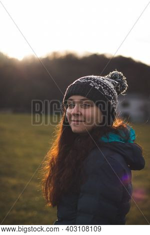 Portrait Of A Beautiful Brown-haired Girl With Blue Eyes At Sunset In Autumn. A Pleasant And Real Sm