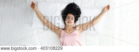 Top View Of Smiling Glad Female Laying On White Bed In Star Position. Relaxed Body And Mind. Cheerfu