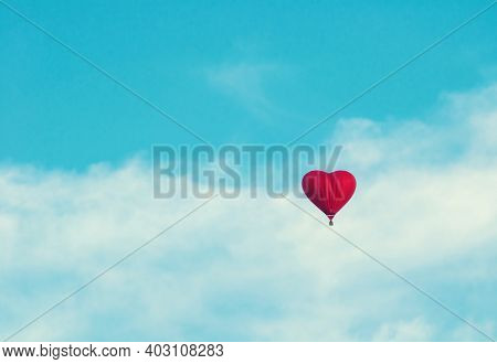 Valentines day background, Valentines day card, Valentines day concept, Valentines day landscape. Red balloon in the the shape of heart in the blue sky. Valentines day concept, Valentines day design, Valentines day background