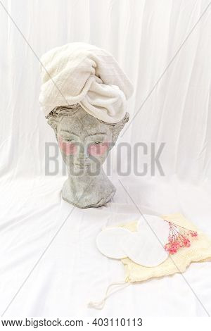 Hydrogel Eye Patches On Sculpture Head In Towel. Reusable Sponges Near Head. Eco Friendly Beauty Con
