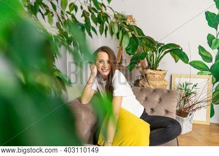 Two Young Women Talk And Drink Coffee On Sofa Indoor. Green Plants Around, Sustainable Design In Int