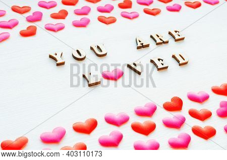 Valentines day background. Valentines card, Valentines composition. Red hearts and inscription You are loved on the white wooden background, Valentines day still life