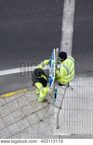 Workers Installing A New Road Sign On Street Sidewalk. Public Maintenance Concept. Copy Space
