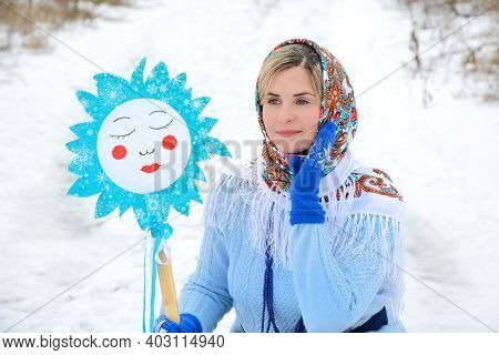 Portrait Of A Beautiful Russian Woman In A White Shawl And Blue Mittens With A Decorative Sun In Her
