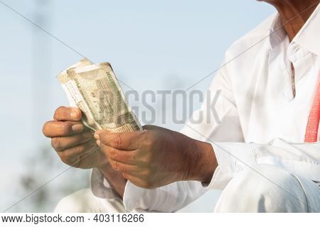 Unrecognisable Indian Farmer Counting Money On Agriculture Field In Trational Dress - Concept Of Goo