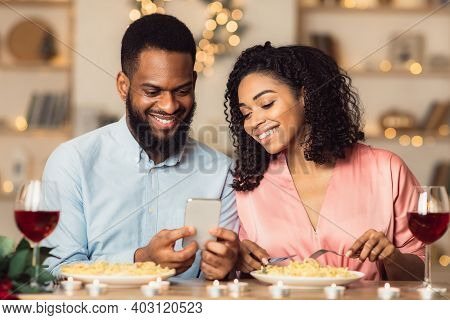 Smiling Young Black Couple Looking At Smartphone And Having Dinner. African American Woman And Man S