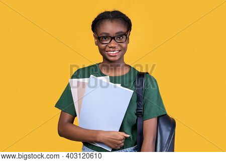 Happy Black Female Student Posing With Books And Notebooks Standing On Yellow Studio Background, Smi