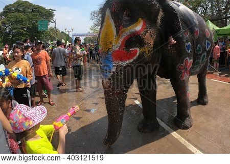 Ayutthaya, Thailand - 14 April 2019: A Boy Happily Spraying Water From A Plastic Gun With Young Elep