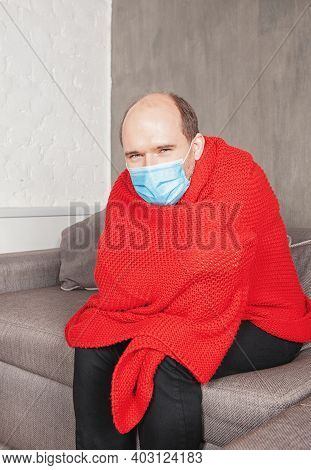 Sad Man Wearing Medical Mask With Headache At Home