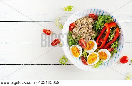 Breakfast Oatmeal Porridge With Green Herbs, Boiled Egg, Tomatoes And Paprika. Healthy Balanced Food