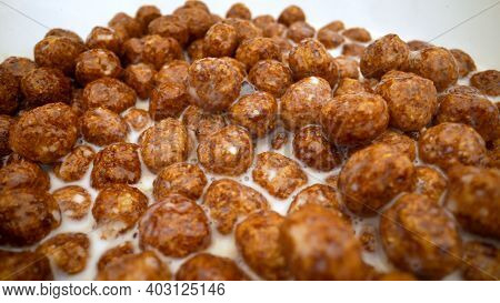 Super Close Up. Milk Is Poured Into Breakfast Cereals Chocolate Corn Balls. Milk Pouring Into Bowl W