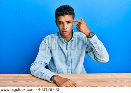 Young handsome african american man wearing casual clothes sitting on the table pointing unhappy to pimple on forehead, ugly infection of blackhead. acne and skin problem