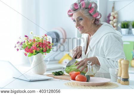 Senior Woman In Hair Rollers Cutting Vegetables On Kitchen Table