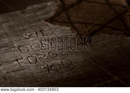 closeup of a ragged jewish badge on a dark rustic wooden surface with the text we do not forget you carved in it