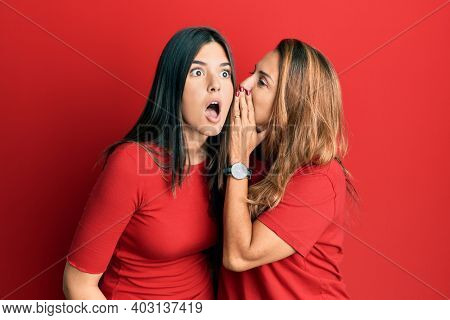 Hispanic family of mother and daughter wearing casual clothes over red background hand on mouth telling secret rumor, whispering malicious talk conversation