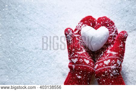 Female hands in knitted mittens with snowy heart against snow background. Love, winter and Valentines day romantic creative concept with copy space for text