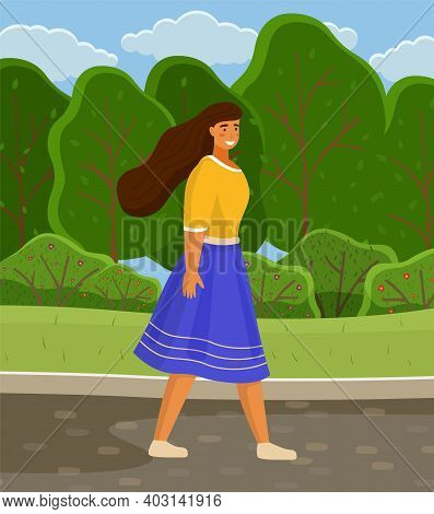 Young Girl In Blue Skirt And Yellow Blouse, With Long Hair Walks In City Park Or Forest. Green Trees